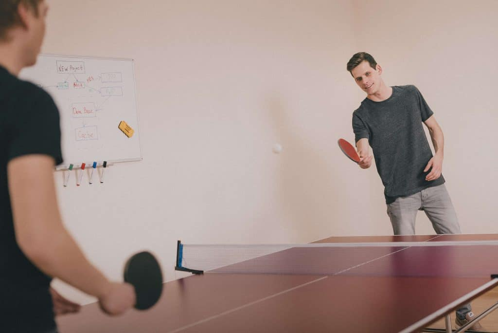 Two co-workers playing ping pong to take a work break.