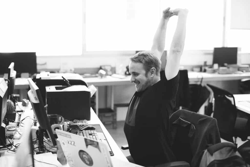 A man stretching and smiling at his desk, feeling accomplished in the open office setting.
