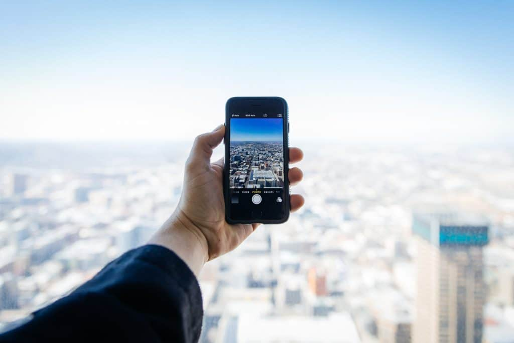 An iphone taking a photo of a city skyline.