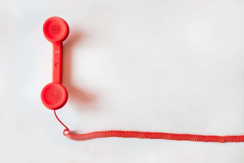 A bright red landline phone on a white background.